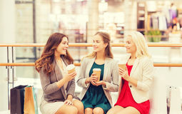 Young women with shopping bags and coffee in mall. Sale, consumerism and people concept - happy young women with shopping bags and coffee paper cups in mall Royalty Free Stock Photo