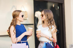Young women with shopping bags and coffee at shop Royalty Free Stock Photo