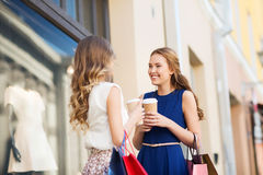 Young women with shopping bags and coffee at shop Stock Images