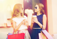 Young women with shopping bags and coffee at shop Stock Image