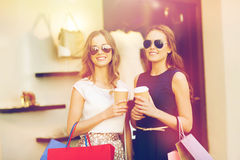 Young women with shopping bags and coffee at shop Stock Photos