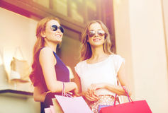 Young women with shopping bags and coffee at shop Stock Photography