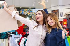 Young women with shopping bags having fun. Beautiful young women with shopping bags having fun in shopping store Royalty Free Stock Photo