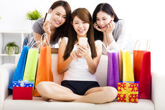 Young women with shopping bags and looking at smart phone Stock Photos