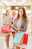 Young women with shopping bags and money in mall. Sale, consumerism and people concept - happy young women with shopping bags and dollar cash money in mall Stock Image