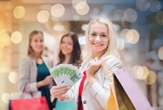 Young women with shopping bags and money in mall. Sale, consumerism and people concept - happy young women with shopping bags and euro cash money in mall Stock Images