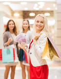Young women with shopping bags and money in mall. Sale, consumerism and people concept - happy young women with shopping bags and euro cash money in mall Royalty Free Stock Images