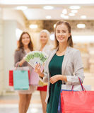 Young women with shopping bags and money in mall. Sale, consumerism and people concept - happy young women with shopping bags and euro cash money in mall Royalty Free Stock Photography
