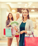 Young women with shopping bags and money in mall. Sale, consumerism and people concept - happy young women with shopping bags and euro cash money in mall Stock Image