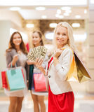 Young women with shopping bags and money in mall. Sale, consumerism and people concept - happy young women with shopping bags and usa dollar cash money in mall Stock Images