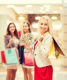 Young women with shopping bags and money in mall. Sale, consumerism and people concept - happy young women with shopping bags and usa dollar cash money in mall Royalty Free Stock Photography