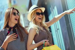 Young women with shopping bags pointing finger to shop window. Happy young women with shopping bags pointing finger to shop window in city Stock Photos