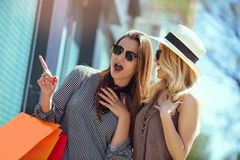 Young women with shopping bags pointing finger to shop window. Happy young women with shopping bags pointing finger to shop window in city Royalty Free Stock Image