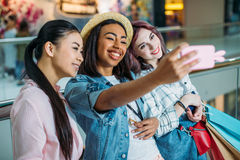 Young women with shopping bags taking selfie, young girls shopping concept. Smiling young women with shopping bags taking selfie, young girls shopping concept Stock Photos