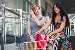 Young women with shopping cart. Two young women with shopping cart against a mall windows Stock Image