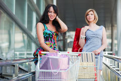 Young fashion women with shopping cart in the mall. Two young fashion women with shopping carts walking in the mall Stock Images