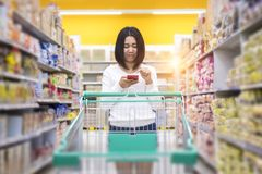 Young women with shopping cart use smartphone stock image