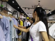 Young women are shopping for clothes during the night at the clothing store Stock Images