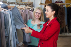Young women shopping jersey. Smiling young women shopping jersey at the apparel store stock photo