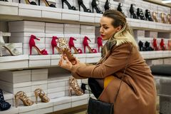 Young women shopping at shoes store. Attractive young woman shopping at shoes store Royalty Free Stock Photos