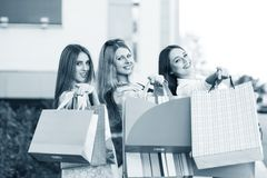 Young women after shopping. Three young women posing on a summer day in the city Royalty Free Stock Image
