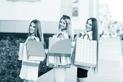 Young women after shopping. Three young women posing on a summer day in the city Stock Image