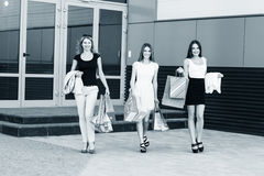 Young women after shopping. Three young women walking on a summer day in the city Stock Image