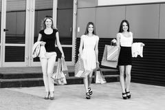 Young women after shopping. Three young women walking on a summer day in the city Stock Images