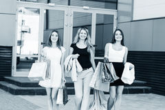Young women after shopping. Three young women walking on a summer day in the city Royalty Free Stock Images