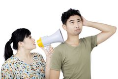 Young woman blaming his husband on studio. Young women shouting through a loudspeaker while blaming his husband, isolated on white background Royalty Free Stock Images