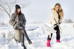 Young women shoveling snow near a small wood Stock Images