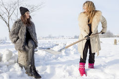 Young women shoveling snow near a small wood Stock Image