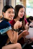 Young woman showing paperwork to her friends. Young women showing paperwork to her friends while sitting together in a coffee shop Stock Images