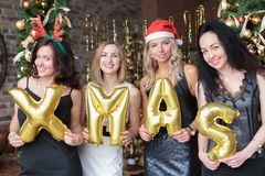Young women showing word xmas made of golden balloons Stock Images