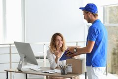 Young woman signing for delivered parcel in office royalty free stock photo