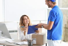 Young woman signing for delivered parcel in office stock photography