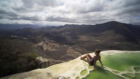 Mexico Hierve el Agua. Young women siting on the brink of mineral pool,crane shot open beautiful view, Mexico Hierve el Agua stock video footage