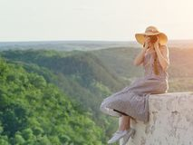 Young women sits on a hill and takes pictures against a forest Royalty Free Stock Images