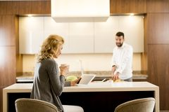 Young woman sits at kitchen table while man preparing food Stock Photo