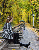 Young women sits on a rails. N a autumn forest stock photo