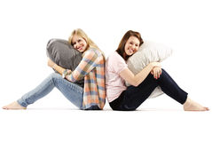 Young women sitting back to back - Indoors Royalty Free Stock Photo
