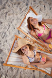 Young women sitting on deck chairs while laughing together Stock Image