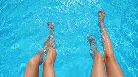 Young women sitting on edge of pool and dangling their feet in water. Two girls with slim tanned legs relaxing near