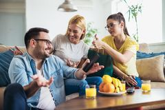 Young women sitting at home with bags after shopping. Young men watching tv royalty free stock photos