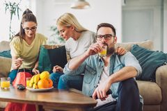 Young women sitting at home with bags after shopping. Young men watching tv Royalty Free Stock Image