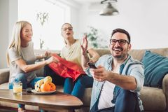 Young women sitting at home with bags after shopping. Young men watching tv Stock Image