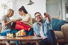 Young women sitting at home with bags after shopping. Young men watching tv Stock Photography