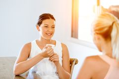 Young woman with her friend having tea at home Royalty Free Stock Photography