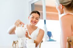 Young woman with her friend having tea at home. Young women sitting at the kitchen table having tea with her friend Stock Photography