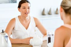 Young woman with her friend having tea at home. Young women sitting at the kitchen table having tea with her friend Stock Image